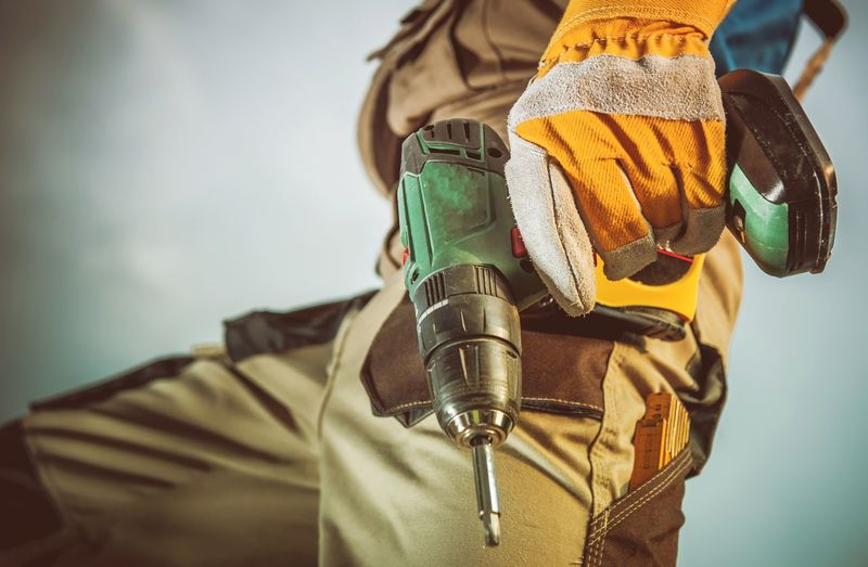 Midsection of manual worker holding drill