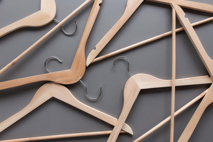 Clothing industry concept on gray background with randomly scattered wooden clothes hangers pattern