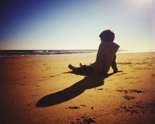 Boy sitting on sand against sea at beach