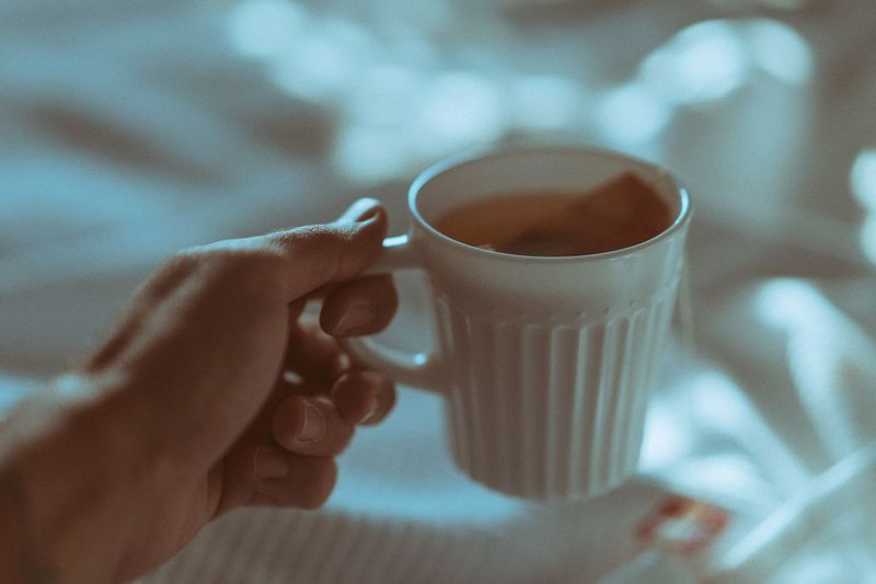 Close-Up Of Human Hand Holding Coffee Cup At Home