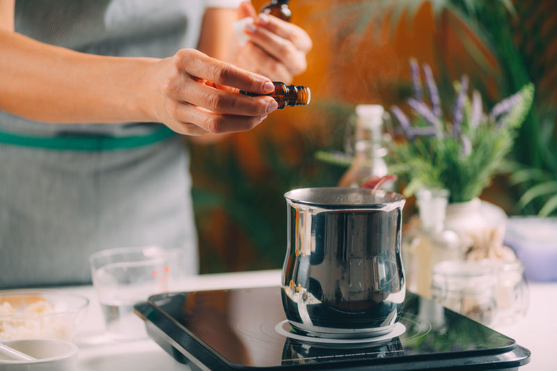 Woman preparing homemade soap with essential oil extracts