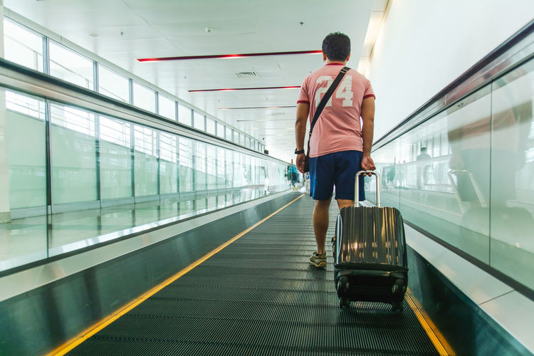 Rear View Real People One Person Transportation Lifestyles Indoors  Men Walking Luggage Motion The Way Forward Architecture Casual Clothing Travel Direction Full Length Airport Standing Leisure Activity Moving Walkway  Terminal Transportation Airplane Rail Transportation Travel Tourism Tourist Businessman