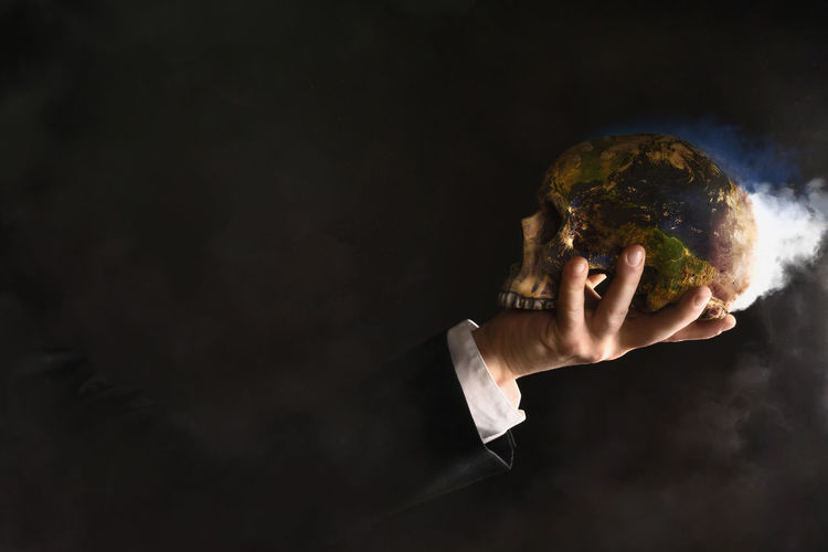 Close-Up Of Hand Holding Skull With Smoke Against Black Background