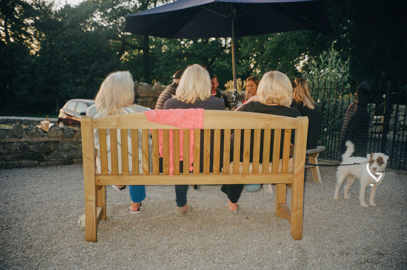 Rear view of women sitting on seat against trees