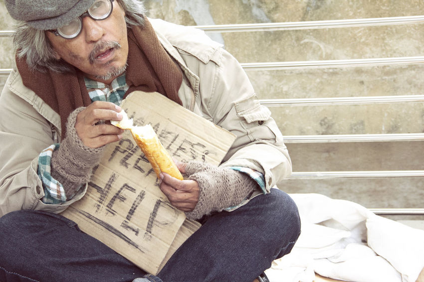 Homeless man on street and eating old bread. Adult Casual Clothing Clothing Eyeglasses  Food Food And Drink Front View Holding Leisure Activity Lifestyles Males  One Person Real People Senior Adult Senior Men Senior Women Sitting Snack Three Quarter Length Warm Clothing Women