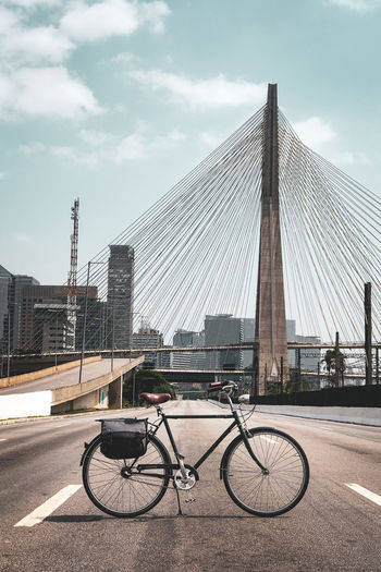 Bicycle parked on bridge against buildings in city against sky