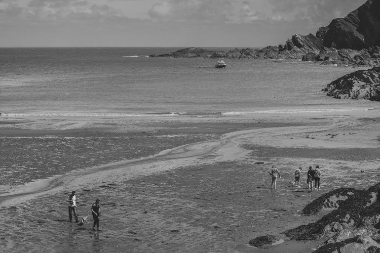 Beach Beauty In Nature Black & White Black And White Coastline Enjoyment Horizon Over Water Idyllic Landscape Leisure Activity Lifestyles Medium Group Of People Nature Outdoors Scenics Sea Monochrome PhotographySky Tourism Tourist Tranquil Scene Tranquility Vacations Water Wave Lost In The Landscape