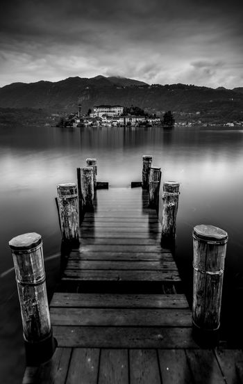 Wooden pier at lake against sky