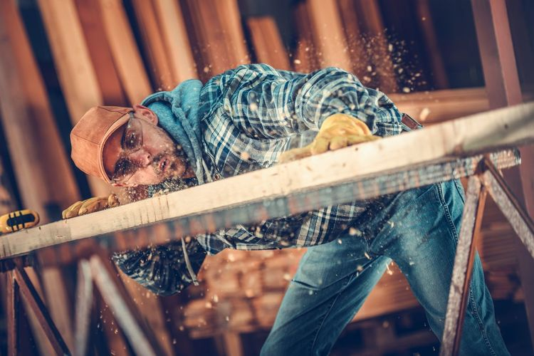 Male carpenter blowing sawdust on workbench
