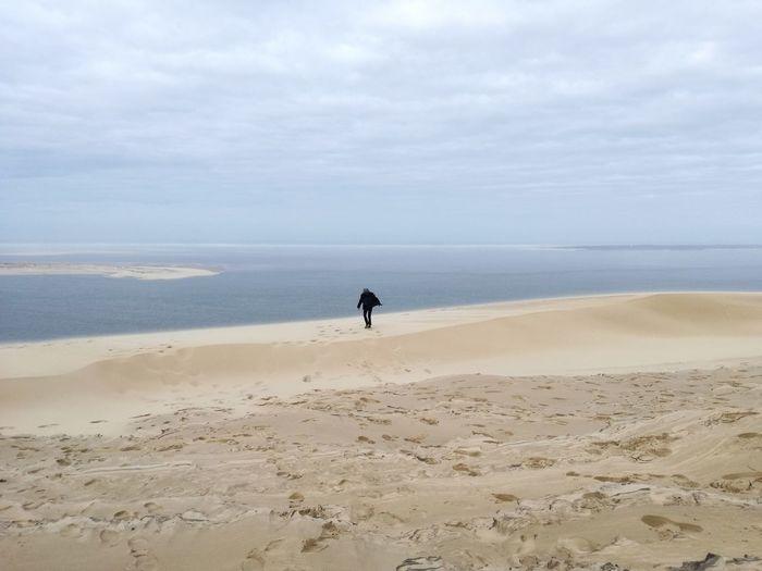 Man walking at beach against sky