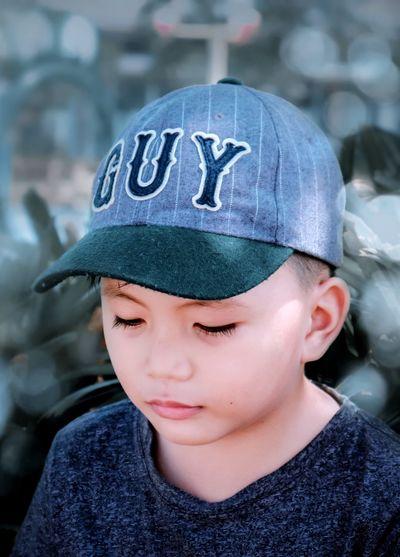 Close-up of boy wearing cap outdoors
