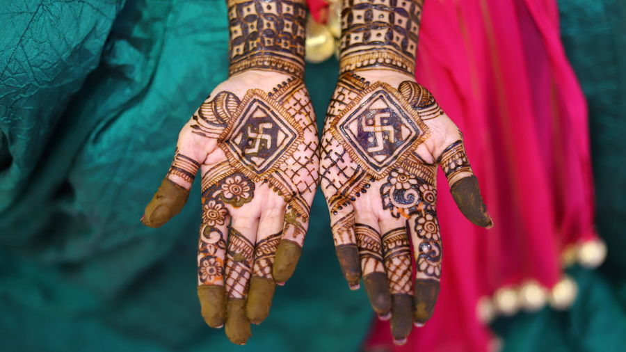 High angle view of woman showing henna tattoo during wedding ceremony