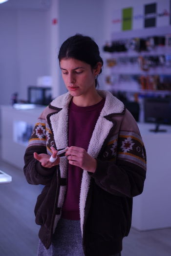 workplace One Person Standing Waist Up Front View Young Adult Indoors  Holding Clothing Three Quarter Length Casual Clothing Looking Focus On Foreground Lifestyles Leisure Activity Real People Warm Clothing Winter Sweater Contemplation Bandage Workplace Winter Coat Woman Portrait Action Comfy  International Women's Day 2019