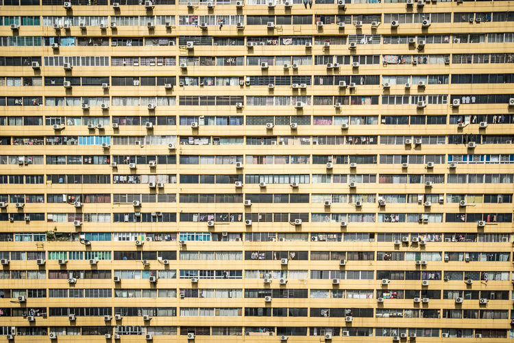 Full frame shot of numerous air conditioning units and windows residential building