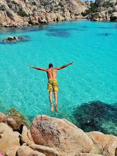 Man's forward jump into the sea with magnificent rear view