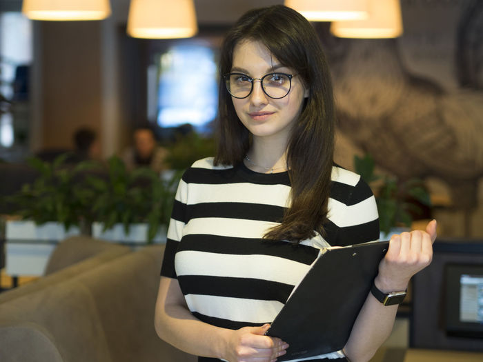 Portrait Of Confident Young Woman With Clipboard Standing In Restaurant