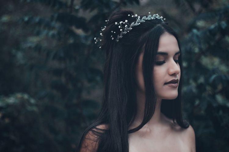 Beautiful young woman wearing tiara against plants