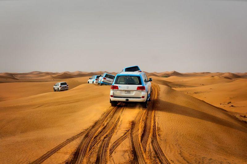 Cars On Sand Dune In Desert Against Sky