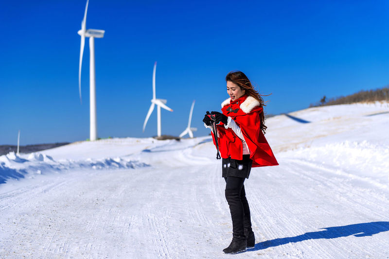 Woman holding camera while standing on snow covered road against wind turbines and clear blue sky