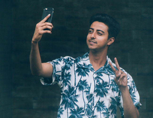 Smiling young man gesturing while taking selfie through mobile phone