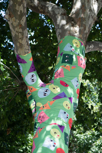 Low section of person wearing multi colored tree trunk