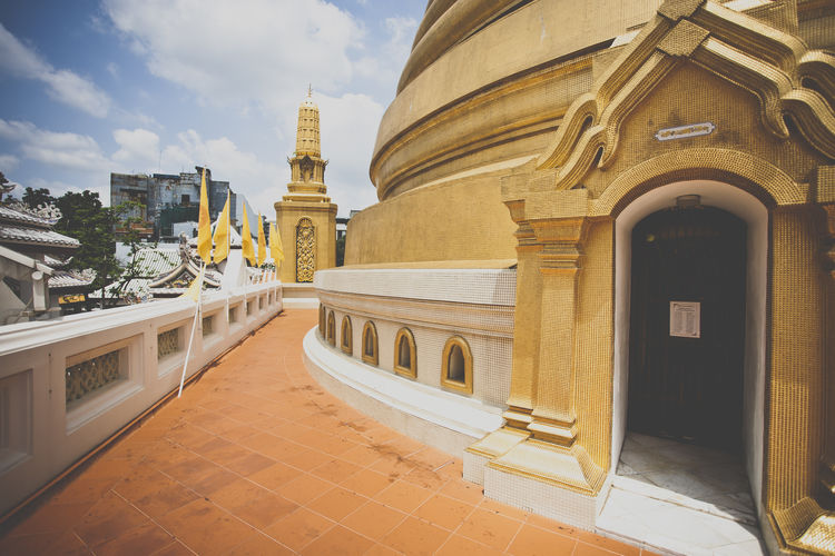 a temple in Thailand Arch Architectural Column Architectural Feature Architecture Buddhism Buddhist Buddhist Temple Building Exterior Built Structure City City Life Day Exterior Gold Golden History In Front Of No People Outdoors Place Of Worship Sky Stone Material Stupa Temple