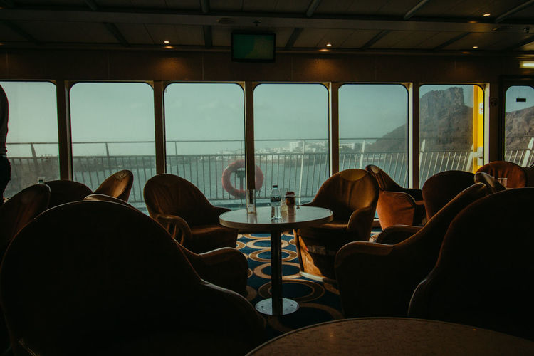 Empty chairs at restaurant in cruise ship