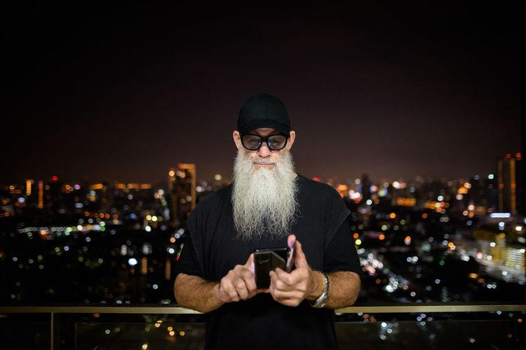 Full length of man using mobile phone at night