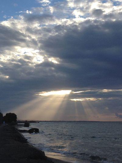 Sun between clouds over sea