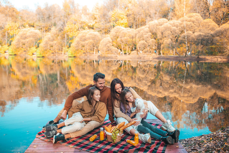 Group of people sitting in lake during autumn