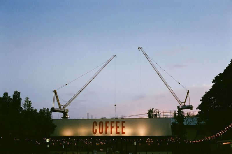 Low angle view of cranes against sky at dusk