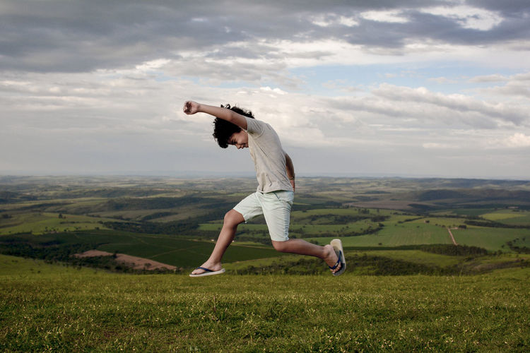 Boy jumping over land against cloudy sky