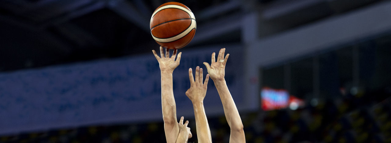 Cropped hands of men catching basketball