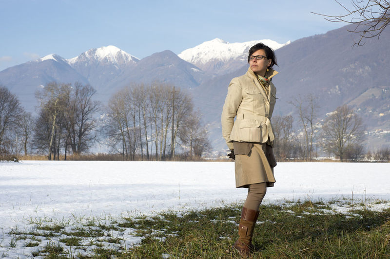 Elegant business woman standing on a snowy field with snow-capped mountain in a sunny day in Ticino, Switzerland. Adult Beauty In Nature Business Cold Temperature Day Elégance Eyewear Landscape Mountain Mountain Range Nature One Person One Woman Only Proud Scenics Selfconfident Skirt Snow Snowcapped Mountain Standing Standing Swiss Alps Tranquility Winter Woman