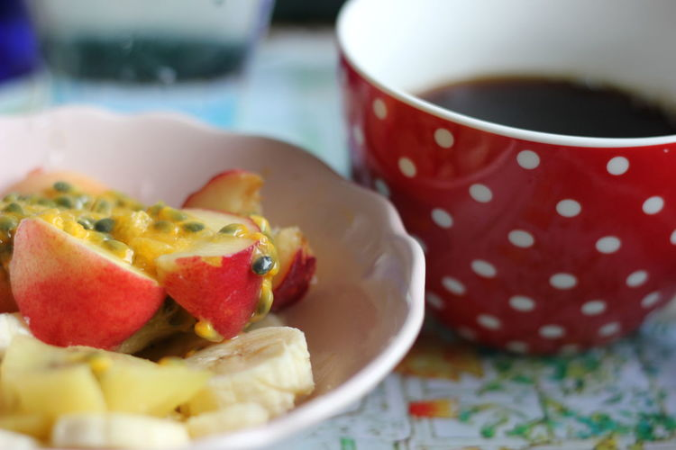 Close-up of fresh fruit salad served with coffee on table