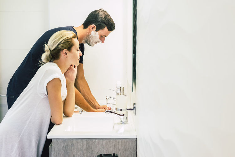 Side view of woman standing by man shaving in bathroom