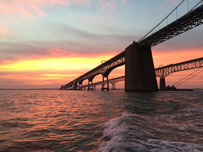 Low angle view of bridge over sea against cloudy sky during sunset
