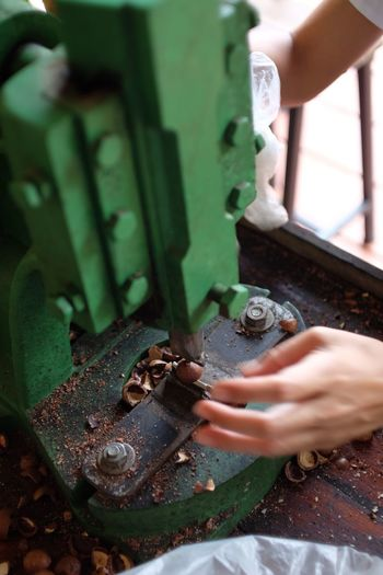 Cropped hands of worker crushing nuts using machine at workshop