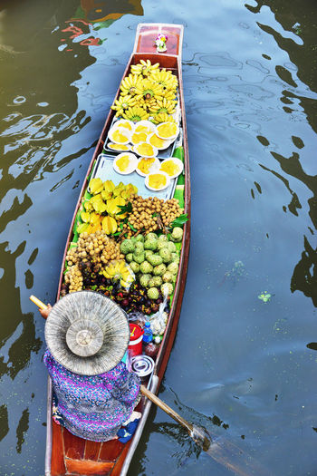 High angle view of woman with various food in boat sailing on river