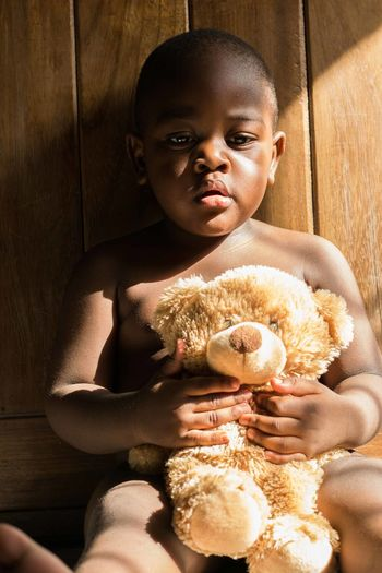 Close-up of cute baby boy holding teddy bear while sitting at home