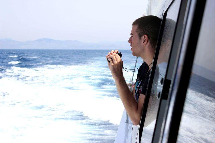 Man Looking Through Window Of Van At Beach