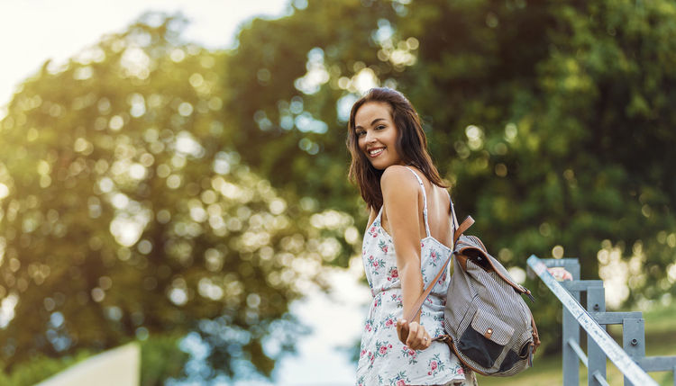 young woman looking at camera Dress Looking At Camera Adult Backpack Bag Beautiful Woman Beauty Brown Hair Brunette Casual Clothing Fashion Hair Happiness Leisure Activity Long Hair Looking At Camera One Person Outdoors Portrait Smiling Summer Three Quarter Length Women Young Adult Young Women
