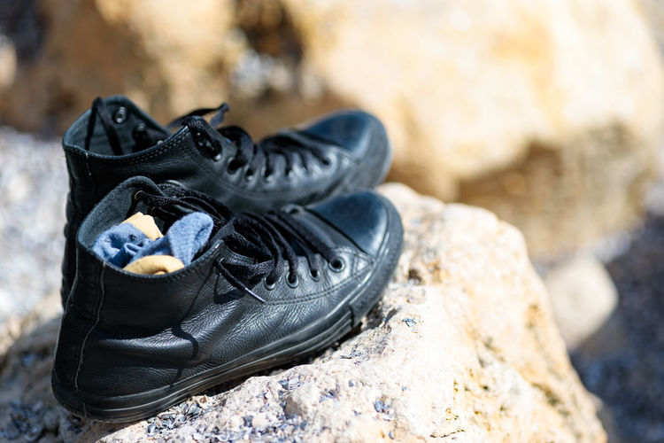 Solid Rock Shoe Rock - Object Black Color Focus On Foreground Outdoors Close-up Nature No People Day Pair Boot Selective Focus Shoelace Personal Accessory Relaxation Still Life Lace - Fastener Leather Beach Life Swimming Alone Alone Time Sneakers Sneakerhead  Sunny Day Waves, Ocean, Nature