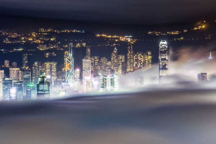 Illuminated Cityscape Covered With Clouds At Night
