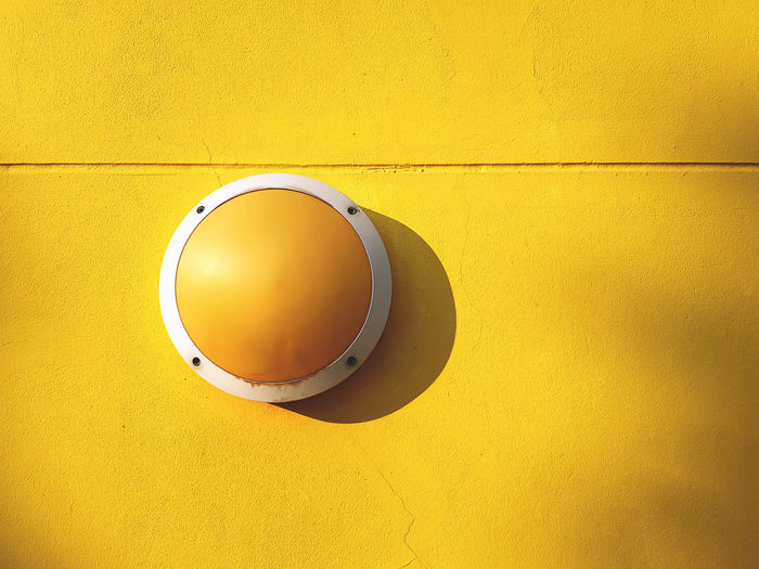Round yellow light luminaire fixture on vivid yellow wall background