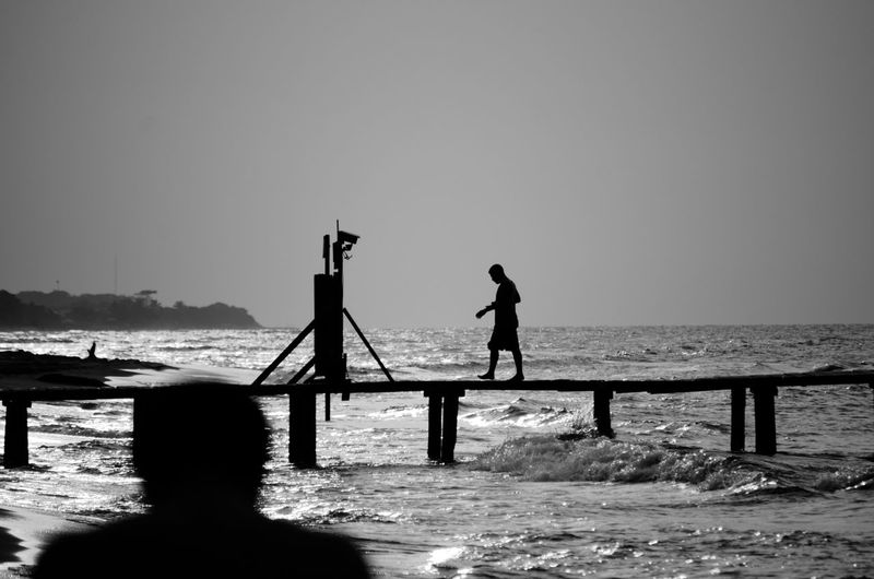 Silhouette man walking on pier over sea against clear sky