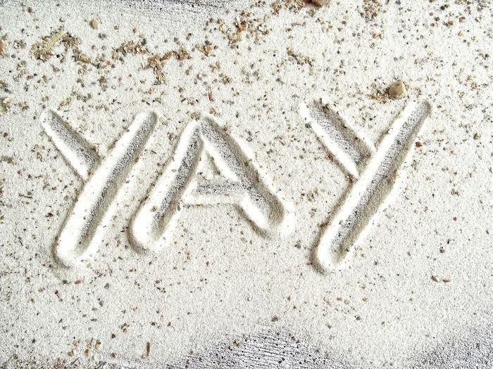High angle view of text on sand