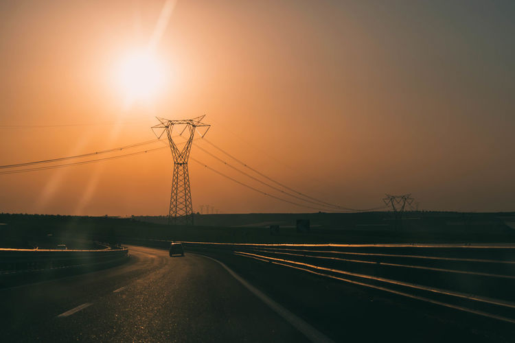 Electricity pylons by road against sky during sunset