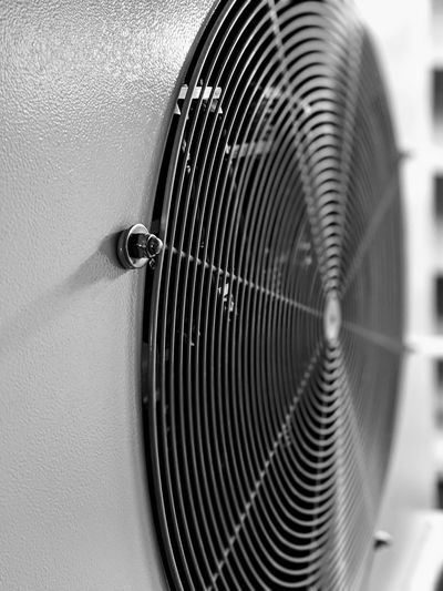 Close-up of electric fan against wall