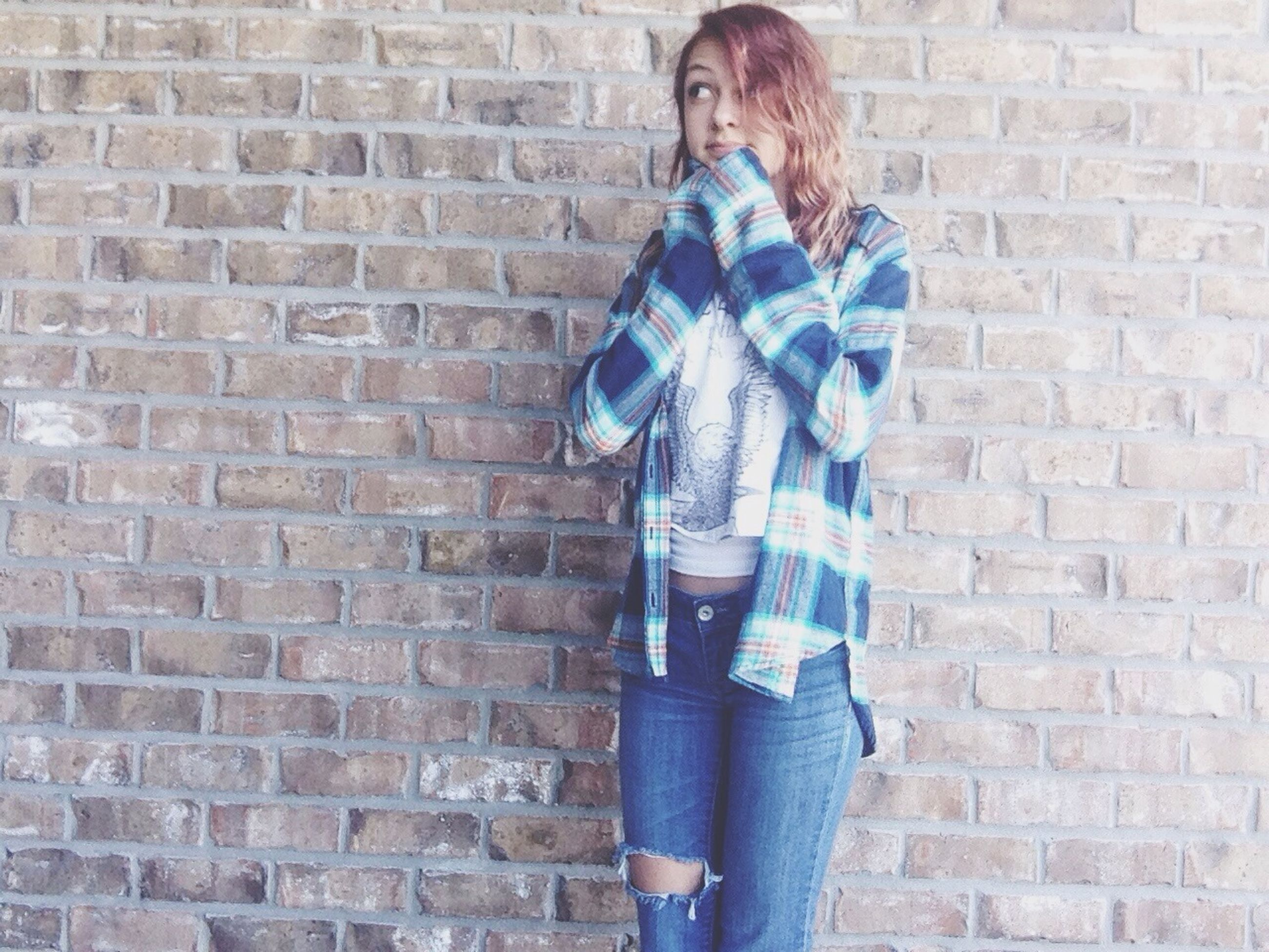 brick wall, wall - building feature, lifestyles, casual clothing, standing, young adult, front view, built structure, architecture, young women, building exterior, leisure activity, wall, person, fashion, three quarter length, stone wall